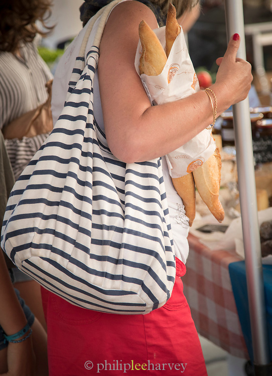 Woman shopping on market, holding baguettes, Llle-Rousse, Corsica, France