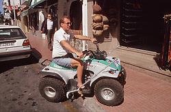 Man with disability riding quad bike; climbing pavement,