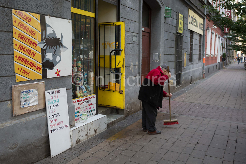A Polish shop keeper sweeps the pavement outside his business,<br /> on 23rd September 2019, in Krakow, Malopolska, Poland.