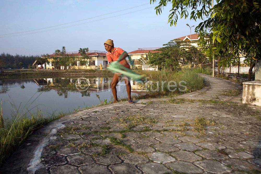 A fisherman, Siva Mani, 62 who works in the Tamaraikulum Elders village, casts his net into the communal pond to catch fish for lunch. Tamil Nadu, India