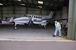 Man with disability; who is wheelchair user; in aircraft hanger preparing to fly plane,