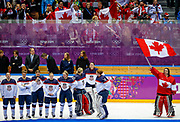 Canada's goalie Shannon Szabados (R) stands with her national flag near Team USA after Canada won their women's gold medal ice hockey game at the Sochi 2014 Winter Olympic Games February 20, 2014. REUTERS/Jim Young