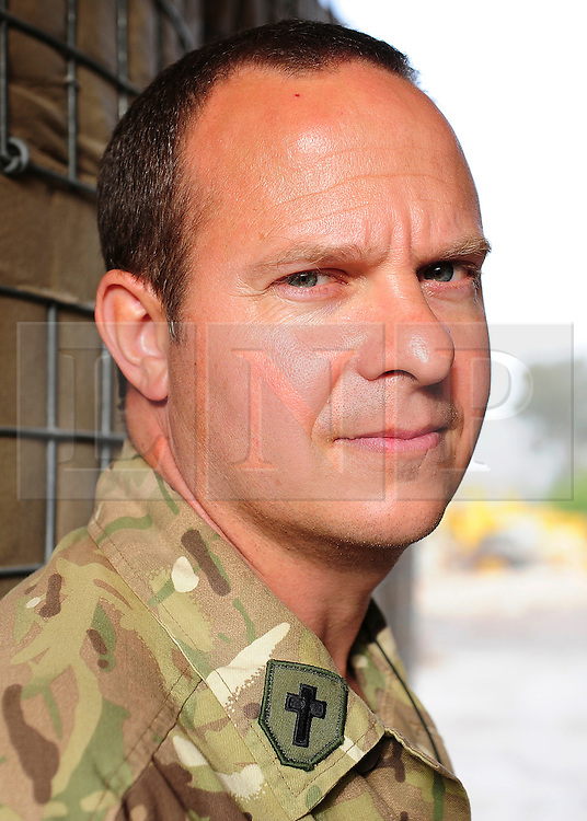"""© licensed to London News Pictures. HELMAND, AFG  21/04/11. Padre Robin Richardson. A British Army chaplain from Sidmouth who is due to finish his tour this Easter Sunday has proved a hit with paratroopers in Helmand Province, handing out crosses made from the wire-mesh that surrounds their base. Padre Robin Richardson (40) a member of 3rd Battalion The Parachute Regiment, has been serving in Afghanistan for the last six months. """"Towards the beginning of the tour, some of the lads asked me if I had some crosses I could give them,"""" he said. """"I found a few at Camp Bastion, and I gave them out. I ran out very quickly.""""..""""So I wandered around our camp at Shahzad, trying to find something I could fashion into a cross. I noticed some discarded Hesco wire, and I saw lots and lots of crosses"""". The wire normally makes up part of the Hesco Bastion fortified walls,  mesh containers with thick liners filled with gravel - that surround military bases across Afghanistan. """"I got busy with some bolt-cutters and a hammer and a drill,"""" said Robin. """"And I started making small crosses out of the discarded wire.""""..""""A lot of the lads have asked if they can have one,"""" he said. """"And they've been wearing them, and understanding a bit about what lies behind it"""". Robin will be returning home to be reunited with his family after six months. """"I've got three sons, aged 13, 11 and 7, and they're fab,"""" he said. """"They give my heart a reason for beating every morning"""". """"The thing I've missed the most has been their smiles"""" he added. """"The first thing I'll do when I get home is give them a hug"""".. Please see special instructions for usage rates. Photo credit should read SGT Alison Baskerville/LNP"""