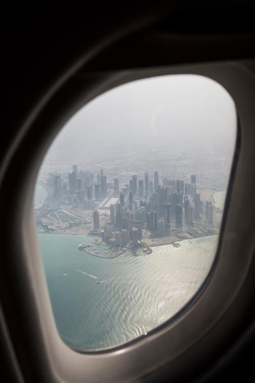 View from an airplane window of the modern city skyline of Doha, Qatar