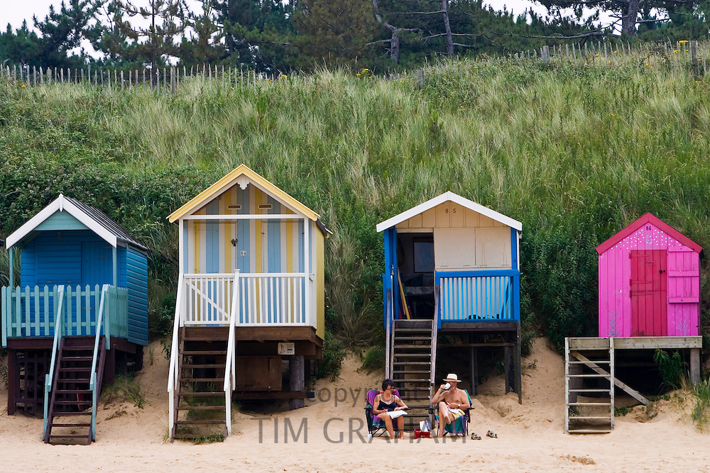 Couple sit outside their beach hut in Wells-Next-The-Sea, Norfolk, United Kingdom