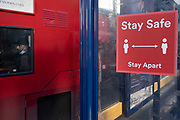 With local coronavirus lockdown measures in place and Birmingham currently set at 'Tier 2' or 'high', people, many of whom are wearing face masks, at bus stops in the city centre, where social distancing measures and signs are in place on 26th October 2020 in Birmingham, United Kingdom. The three tier system in the UK has levels: 'medium', which includes the rule of six, 'high', which will cover most areas under current restrictions; and 'very high' for those areas with particularly high case numbers. Meanwhile there have been calls by politicians for a 'circuit breaker' complete lockdown to be announced to help the growing spread of the Covid-19 virus.