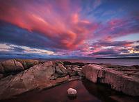 Beautiful clouds light up the sky along the rocky coast of Maine, Acadia National Park, Maine, USA