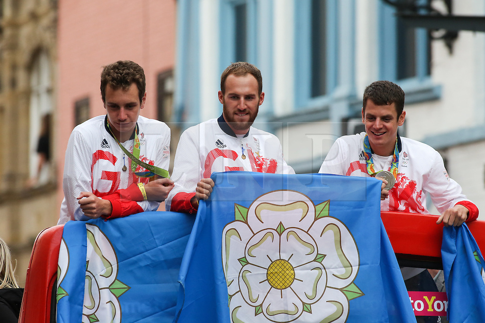 © Licensed to London News Pictures. 28/09/2016. Leeds, UK. Alistair Brownlee, Gordon Benson and Jonathan Brownlee atop an open top bus at the Olympic and Paralympic parade in Leeds. Yorkshire's Olympic and Paralympic stars receive a heroes' welcome during an open top bus parade in Leeds, West Yorkshire. . Photo credit : Ian Hinchliffe/LNP