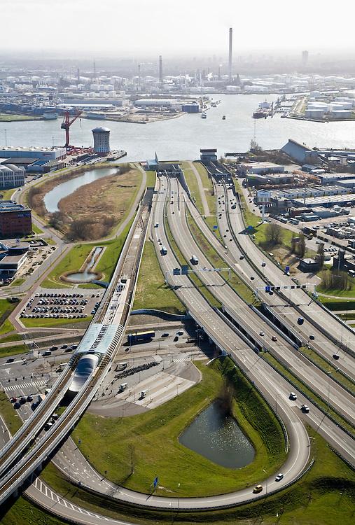 Nederland, Zuid-Holland, Schiedam, 04-03-2008; autosnelweg A4 met op- en afritten, toerit naar de Beneluxtunnel; rivier de Nieuwe Maas aan de horizon, methet hoofdkantoor van de Mammoet-van Seumeren Group (Groep) -  naast de rode kraan; links in beeld de metrolijn naar Hoogvliet (Calandlijn) met station Vijfhuizen en het het bedrijventerrein Vijhuizen (op  het terrein van de voormalige werf Wilton-Fijenoord); aan de horizon - met schoorstenen de Shell olieraffinaderij in Pernis;  A4 motorway with exit and entry, ramps to the Benelux Tunnel entrance, River Maas on the horizon, with the headquarters of the Mammoet- or Seumeren Group (Group)on the horizon - chimneys with the Shell oil refinery in Pernis.    .luchtfoto (toeslag); aerial photo (additional fee required); .foto Siebe Swart / photo Siebe Swart