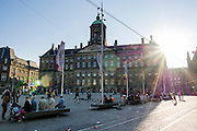 Het paleis op de Dam in Amsterdam in tegenlicht op een zomerse avond. Het paleis is tussen 1648 en 1665 gebouwd als stadhuis en ontworpen door Jacob van Campen. <br /> <br /> The palace on the Dam in Amsterdam in backlight on a summer evening. It's build between 1648 and 1665 as a town hall and was designed by Jacob van Campen.