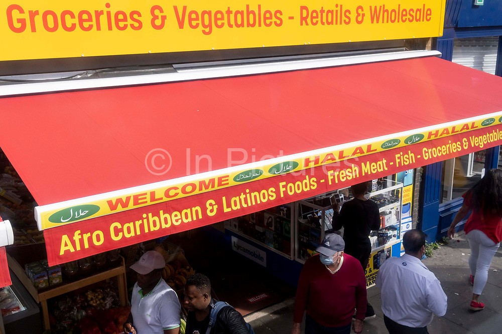 Groceries, vegetables from Afro Caribbean and Latin countries and including Halal meats, are advertised on the awning of a high street retailer in south London, on 13th September 2021, in London, England.
