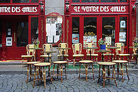 Empty straw colored cafe chairs and tables sit in a street paved with grey paving stones in front of a bistro with red walls and tall windows in St. Malo, Brittany, France. Potted flowers sit on the tables.