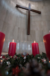 8 December 2019, Madrid, Spain: Candlelight glows on the altar table under the church's large wooden cross, as Christians from around the globe gather with local congregants in the Iglesia de Jesús in central Madrid, to celebrate an ecumenical prayer service during COP25.
