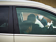 """11 APRIL 2020 - DES MOINES, IOWA: JORDON ELWELL, owner and CEO of Midwest Foods, talks to a passing motorist during a food distribution in Des Moines. Most non-essential businesses in Iowa are closed until 30 April. Because of business closings causes by the Novel Coronavirus (SARS-CoV-2) pandemic, well over 100,000 Iowans filed first time claims for unemployment in the last three weeks, more than applied during the peak of the Great Recession of 2008. Local food banks have seen an unprecedented spike in people seeking nutritional assistance. Midwest Foods, a Des Moines based company and owner of Ginos Fine Italian Foods, gave away 1,000 complete dinners with sauce, noodles, salad, and dressing Saturday morning. People started lining up 3 hours before the food distribution began. The food distribution was done following """"social distancing"""" guidelines and all of the workers wore masks and gloves.     PHOTO BY JACK KURTZ"""