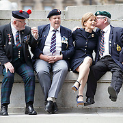 Armed Forces Day 2015.  First Minister Nicola Sturgeon with the green beret of the commandos as she poses for pictures with ex-service men. L to R : Michael Madden of Black Watch, Graeme Dickson of Royal Transport and  John Bannerman of the Royal Marines.  Glasgow. Picture Robert Perry 27th June 2015<br /> <br /> Must credit photo to Robert Perry<br /> FEE PAYABLE FOR REPRO USE<br /> FEE PAYABLE FOR ALL INTERNET USE<br /> www.robertperry.co.uk<br /> NB -This image is not to be distributed without the prior consent of the copyright holder.<br /> in using this image you agree to abide by terms and conditions as stated in this caption.<br /> All monies payable to Robert Perry<br /> <br /> (PLEASE DO NOT REMOVE THIS CAPTION)<br /> This image is intended for Editorial use (e.g. news). Any commercial or promotional use requires additional clearance. <br /> Copyright 2014 All rights protected.<br /> first use only<br /> contact details<br /> Robert Perry     <br /> 07702 631 477<br /> robertperryphotos@gmail.com<br /> no internet usage without prior consent.         <br /> Robert Perry reserves the right to pursue unauthorised use of this image . If you violate my intellectual property you may be liable for  damages, loss of income, and profits you derive from the use of this image.