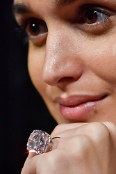 "© Licensed to London News Pictures. 13/10/2017. London, UK. A model presents ""The Raj Pink"" diamond at a preview at Sotheby's New Bond Street.  It is the world's largest known fancy intense pink diamond weighing 37.30 carats and will be offered for sale by Sotheby's in Geneva on 15 November at an estimate of US$20-30m. Photo credit : Stephen Chung/LNP"