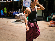 30 APRIL 2013 - MAHACHAI, SAMUT SAKHON, THAILAND:  A Burmese man wearing a traditional longyi (Burmese sarong) walks through the Thai fishing port of Mahachai. The Thai fishing industry is heavily reliant on Burmese and Cambodian migrants. Burmese migrants crew many of the fishing boats that sail out of Samut Sakhon and staff many of the fish processing plants in Samut Sakhon, about 45 miles south of Bangkok. Migrants pay as much $700 (US) each to be smuggled from the Burmese border to Samut Sakhon for jobs that pay less than $5.00 (US) per day. There have also been reports that some Burmese workers are abused and held in slavery like conditions in the Thai fishing industry.          PHOTO BY JACK KURTZ