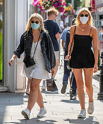 © Licensed to London News Pictures. 22/07/2020. London, UK. Shoppers enjoy the warm sunshine on the King's Road in Chelsea despite the stuffy masks as weather forecasters predict 26c today as Londoners get ready for Friday when masks become compulsory in shops in England. Photo credit: Alex Lentati/LNP