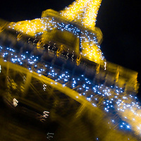 The Eifel Tower in Paris, France with twinkling lights dancing at night.  By night The Eiffel Tower dances in sparkling lights.