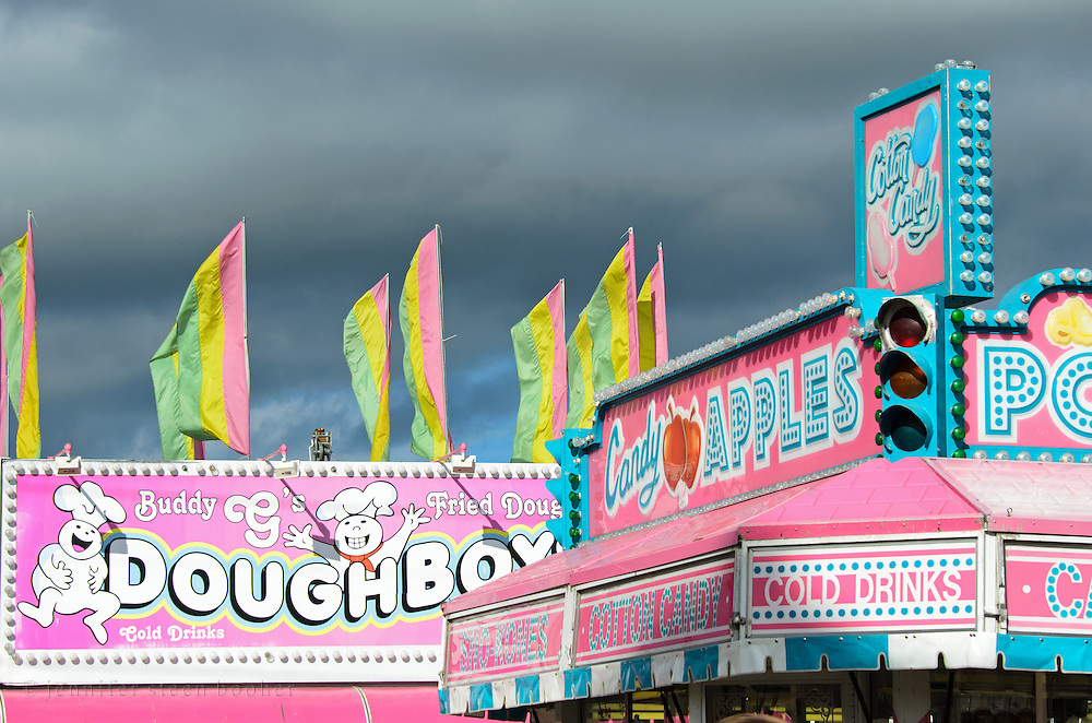 Food stalls at the Blue Hill Fair lit by afternoon sunlight against dark gray rain clouds