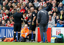 Match referee Bobby Madley (centre) leaves the game and  colleague Jon Moss (left) takes over as referee