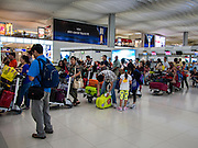 14 AUGUST 2013 - HONG KONG:  Passengers line up to rebook flights and check in at Hong Kong International Airport. Dozens of flights were delayed at one of the busiest airports in Asia and Hong Kong raised their alert to level 8, the highest, and closed schools and many businesses because of Severe Typhoon Utor. The storm passed within 260 kilometers of Hong Kong before making landfall in mainland China. Severe Typhoon Utor (known in the Philippines as Typhoon Labuyo) is an active tropical cyclone located over the South China Sea. The eleventh named storm and second typhoon of the 2013 typhoon season, Utor formed from a tropical depression on August 8. The depression was upgraded to Tropical Storm Utor the following day, and to typhoon intensity just a few hours afterwards. The Philippines, which bore the brunt of the storm, reported 1 dead in a mudslide and 23 fishermen missing at sea.  PHOTO BY JACK KURTZ