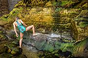 Mallorca, Cala Banyalbufar, Girl is taking a shower in a waterfall on the beach. 29-7-2018