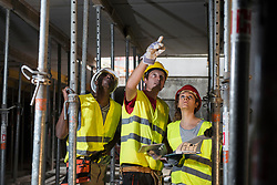 Construction workers with digital tablet and architectural plan at building site, Munich, Bavaria, Germany