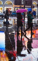 London, December 31 2017. The umbrellas come out as a downpour begins in London's west end ahead of the New Year's Eve fireworks at midnight. PICTURED: People make their way past a determined busker on the wet pavements of Piccadilly Circus. © SWNS