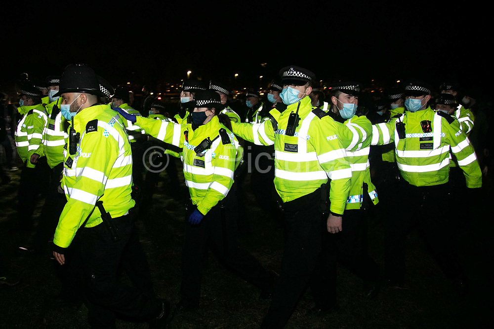 Hundreds of people gathered  at a peaceful vigil for Sarah Everard on Clapham Common in South London on the 13th of March 2021, London, United Kingdom. Sarah Everard went missing on 3 March after setting off at 9pm from a friend's house to make her two and a half mile journey home. The police retreats out of the common in an orderly fashion. The vigil was also a call to end violence against girls and women perpetrated by men. The vigil was not sanctioned by police because of Covid restrictions and the police decided to arrest a number of people in an attempt to end the peaceful and highly emotional vigil. The event took place at the band stand on the common and speeches were held from the stand till police confiscated the sound equipment.