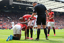 30th April 2017 - Premier League - Manchester United v Swansea City - Ashley Young of Man Utd checks on injured teammate Marcus Rashford as referee Neil Swarbrick looks on - Photo: Simon Stacpoole / Offside.