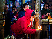 07 MARCH 2017 - KATHMANDU, NEPAL: A woman presents offerings to a volunteer at the Kamaladi Ganesh Temple, the most important Hindu temple dedicated to Ganesh, known as the overcomer of obstacles, in Kathmandu. In Hindu theology, Tuesdays are the best day to pray to Ganesh and the temple is very busy on Tuesdays. People frequently visit temples dedicated to Ganesh when they buy a new home or start a new job.     PHOTO BY JACK KURTZ