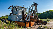 Dredge No. 4, a National Historic Site of Canada, was the largest wooden-hulled dredge in North America. Operating from 1913 until 1959, it recovered 8 metric tones of gold. After nearly 30 years on the Klondike River, it was re-built near the mouth of Bonanza Creek to run for another 18 years before sinking where seen now, along Bonanza Creek Road 13 kilometres (8.1 mi) south of the Klondike Highway near Dawson City, Yukon, Canada. A hydro-electric dam 60 km away powered the massive water pumps, winches, and 72-bucket line to sluice gold from river gravel, 24-7 from late April or early May until late November each season, and sometimes throughout winter. Vast river beds were upended into tailing piles, including 26 homes, as the ongoing Placer Mining Act gave mining rights precedence over surface rights. Dawson City was the center of the Klondike Gold Rush (1896–99), after which population rapidly declined, in Yukon, Canada. Dawson City shrank further during World War II after the Alaska Highway bypassed it 300 miles (480 km) to the south using Whitehorse as a hub. In 1953, Whitehorse replaced Dawson City as Yukon Territory's capital. Dawson City's population dropped to 600–900 through the 1960s-1970s, but later increased as high gold prices made modern placer mining operations profitable and tourism was promoted. In Yukon, the Klondike Highway is marked as Yukon Highway 2 to Dawson City. This image was stitched from multiple overlapping photos.