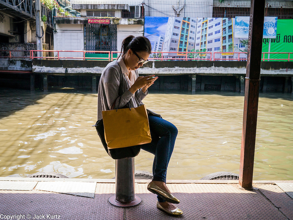 10 OCTOBER 2012 - BANGKOK, THAILAND:  A woman checks her smart phone while she waits for a Khlong Saen Saeb passenger boat at the AsokPetchaburi Pier in Bangkok. Bangkok used to be criss crossed by canals (called Khlongs in Thai) but most have been filled in and paved over. Khlong Saen Saeb is one of the few remaining khlongs in Bangkok with regular passenger boat service. Boats and ships play an important in daily life in Bangkok. Thousands of people commute to work daily on the Chao Phraya Express Boats and fast boats that ply Khlong Saen Saeb. Boats are used to haul commodities through the city to deep water ports for export.     PHOTO BY JACK KURTZ