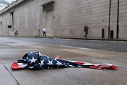 After a rain shower, an American Stars and Stripes flag bandana lies on the wet pavement opposite the high wouter wall of the Bank of England in the City of London, the UK capital's financial district, on 17th August 2020, in the City of London, England.