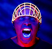 Screaming man with glowing face guard on his head.Black light