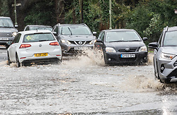 © Licensed to London News Pictures. 16/02/2020. Surrey, UK. Flooding on the A244 Leatherhead Road in Oxshott caused delays as the Met Office issue an Amber Alert for heavy rain in Surrey as Storm Dennis sweeps across the South East with high winds and more rain for Sunday. Photo credit: Alex Lentati/LNP