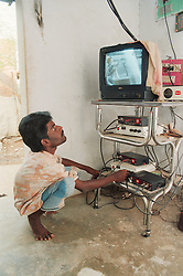 Indian cable operator affected by polio; member of selfhelp group supported by charity ADD India; adjusting television wires and monitoring reception,