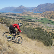 Ben Tyas from Queenstown in action during the New Zealand South Island Downhill Cup Mountain Bike series held on The Remarkables face with a stunning backdrop of the Wakatipu Basin. 150 riders took part in the two day event. Queenstown, Otago, New Zealand. 9th January 2012. Photo Tim Clayton