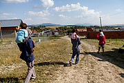Three generations (from left grandfather Rudolf and grandson Kevin, his son Rudo with his daughter and Emil with his son) walking down from the construction side to the village. They and their families joined a micro loan program for the local Roma community supported by a Slovak foundation and a construction supervisor to built their own low cost house themselves, on land they own.