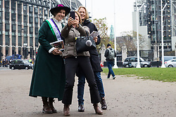 London, UK. 6th November, 2018. Activists from Feminist Fightback dressed as suffragettes change the sign on the new Millicent Fawcett statue in Parliament Square from 'Courage calls to Courage Everywhere' to 'Feminists demand healthcare for all' in protest against NHS charges for migrants. Under the new NHS charging system, migrants not considered 'settled' in the UK are being charged up to £7000 for pregnancy care and £1300 for an abortion in an NHS hospital. Charging has a deterrent effect on women's access to maternity care, posing risks to their pregnancies and the health of their babies, and anxiety about charging has an adverse effect on maternal mental health with consequent effects on women's pregnancies and pregnancy outcomes.