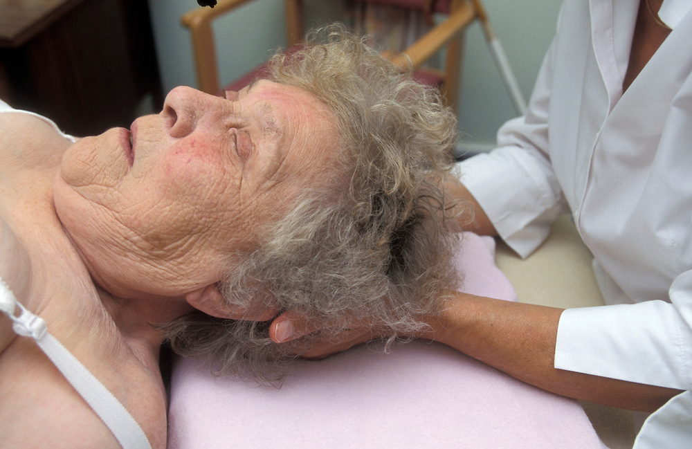 Elderly woman having a neck / head massage, UK