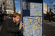 A visitor examines one of the many street maps of central London, this one located near Leicester Sq tube station.