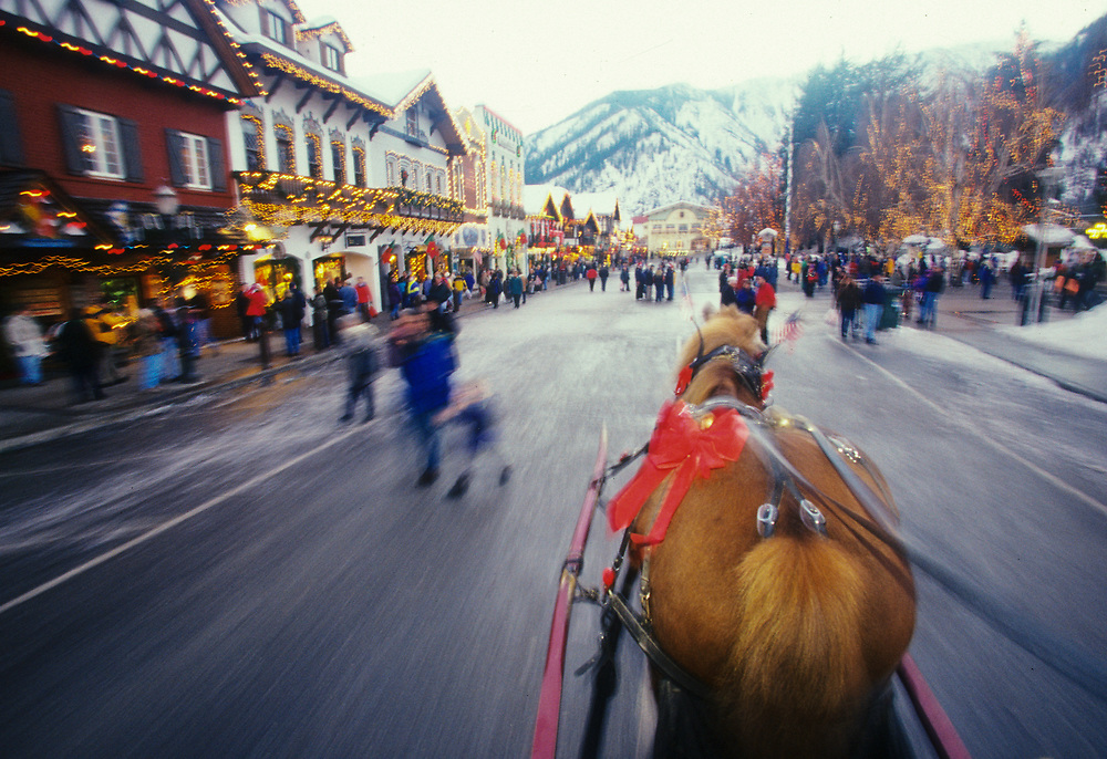 North America, United States, Washington, Leavenworth, view from horse-drawn carriage of Front Street with Christmas lights during holiday festival