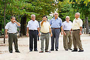 Men stand in a line while one takes aim in a traditional game of bochas, or petanque, in Parque del Buen Retiro, Madrid, Spain, the country's largest city park.