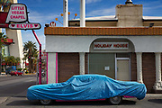 Covered pink car outside Las Vegas wedding chapel and motel with Elvis sign,