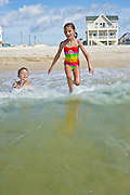 Four kids hold hands and jump while playing on the beach.