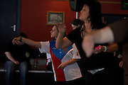 An unknown Czech Republic ladies darts player throws darts surrounded by mostly English women during tournament
