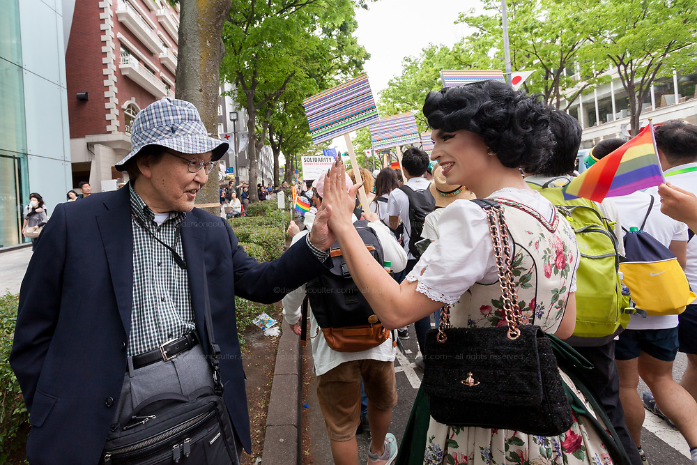 """Austrian Drag Queen, Tamara Mascara (right) gives an older Japanese man a """"High Five"""" as he shows his support for LGBT issues at the sixth annual Tokyo Rainbow Pride event, Tokyo, Japan. Sunday May 7th 2017. Tokyo's  colourful and energetic Rainbow Pride Week runs from April 29th to May 7th in 2017 with Lesbian, Gay, Bisexual and Transgender (LGBT) awareness raising events throughout the week culminating in the Rainbow Pride Parade on Sunday May 7th."""