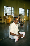 Sundarpaul at prayer during a religious service held every morning at dawn in the  community hall. Tamaraikulum Elders village, Tamil Nadu, India